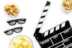 Aliments de préparation rapide pour le film de observation Maïs éclaté, chips, biscottes près des verres et claquette sur la vue  Photographie stock