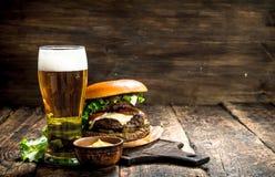 Aliments de préparation rapide Un grand hamburger avec du boeuf et un verre de bière Photos stock