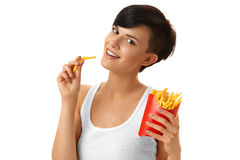 Aliments de préparation rapide Fille mangeant des pommes frites Fond blanc Nourriture concentrée Images stock