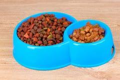 Aliments pour chats secs dans des cuvettes sur en bois Photographie stock libre de droits