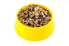 Aliments pour chats secs dans la cuvette jaune d'isolement sur le fond blanc Photos libres de droits