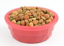 Aliments pour chiens secs dans une cuvette rose photographie stock