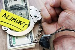 Alimony and hand in handcuffs. Legal separation. Cash as Alimony and hand in handcuffs. Legal separation Royalty Free Stock Photos