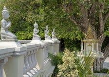 Alinéese de rogar las estatuas de Buda que se arrodillan con las manos junto imagen de archivo
