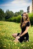 Alineada de la muchacha en la hierba con los dientes de león Imagenes de archivo