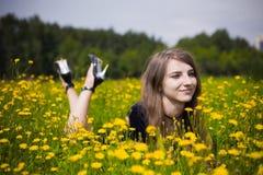 Alineada de la muchacha en la hierba con los dientes de león Fotos de archivo