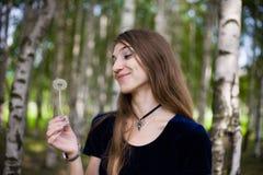 Alineada de la muchacha en la hierba con los dientes de león Imagen de archivo libre de regalías