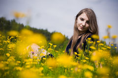 Alineada de la muchacha en la hierba con los dientes de león Fotografía de archivo libre de regalías