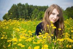 Alineada de la muchacha en la hierba con los dientes de león Fotos de archivo libres de regalías