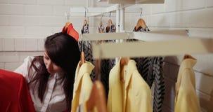 Alineada de la ropa de la mujer del comprador que intenta mientras que hace compras en tienda de la ropa durante venta La muchach almacen de metraje de vídeo