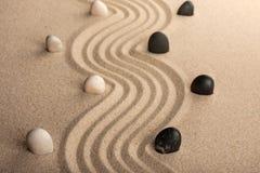 Alinee las piedras blancos y negros, colocándose en la arena Imagenes de archivo