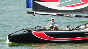 Alinghi skipper steering boat at Extreme Sailing Series Singapore 2013. Alinghi skipper steering the boat at the Extreme Sailing Series race at Marina Bay royalty free stock images