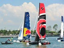 Alinghi som springer Red Bull som seglar laget på den extrema segla serien Singapore 2013 Arkivfoton