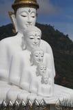 Alinhamento branco de assento do poço da estátua de buddha na frente da montanha Imagem de Stock
