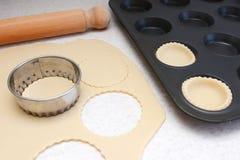 Alinhando uma lata do bolo com círculos da pastelaria desenrolada Fotos de Stock