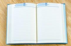 Alinhar-caderno aberto no fundo de madeira marrom Imagem de Stock Royalty Free