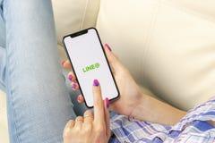 Alinhe o ícone da aplicação no close-up da tela do iPhone X de Apple nas mãos da mulher Linha ícone do app A linha é uma rede soc Imagem de Stock