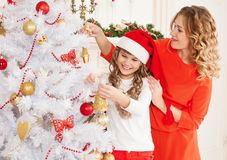 Alisa&Alexandra. Christmas  girl  and mother red cap and tree to Royalty Free Stock Images