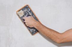Alisando paredes emplastradas, esponja da construção fotografia de stock royalty free