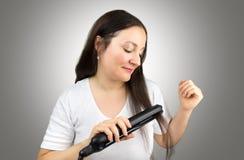 Alisar mi pelo con el hierro plano imagen de archivo libre de regalías
