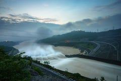 Alise salir el agua de la presa hidroeléctrica en el amanecer Imagenes de archivo