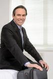 Aliste para ir. Hombre de negocios maduro alegre que se sienta en el sofá en Foto de archivo libre de regalías