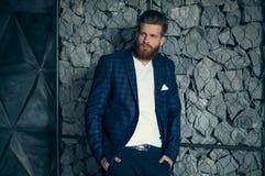Aliste para ir Hombre hermoso con el pelo largo y barba que mira de mirada de lado mientras que se opone a fondo gris imagen de archivo