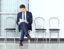 Aliste para la entrevista Hombre pensativo en el formalwear que sostiene el papel Imagen de archivo