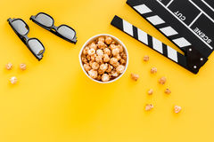 Aliste para mirar la película Clapperboard, vidrios y palomitas en copyspace amarillo de la opinión superior del fondo Imagenes de archivo