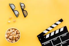 Aliste para mirar la película Clapperboard, vidrios y palomitas en copyspace amarillo de la opinión superior del fondo Fotografía de archivo