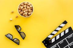 Aliste para mirar la película Clapperboard, vidrios y palomitas en copyspace amarillo de la opinión superior del fondo Fotos de archivo