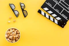 Aliste para mirar la película Clapperboard, vidrios y palomitas en copyspace amarillo de la opinión superior del fondo Foto de archivo libre de regalías
