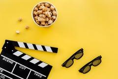 Aliste para mirar la película Clapperboard, vidrios y palomitas en copyspace amarillo de la opinión superior del fondo Fotos de archivo libres de regalías