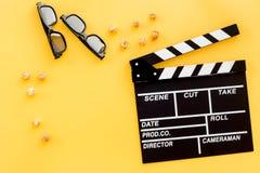 Aliste para mirar la película Clapperboard, vidrios y palomitas en copyspace amarillo de la opinión superior del fondo Imagen de archivo