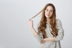 Aliste para oírle hacia fuera y para ayudar con la sugerencia Adolescente atractivo despreocupado que juega con el pelo y que par imágenes de archivo libres de regalías