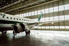 Alitalia Embraer en hangar Fotografía de archivo libre de regalías