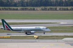 Alitalia Embraer erj190 que lleva en taxi para bloquear en el aeropuerto de Viena Imagen de archivo libre de regalías