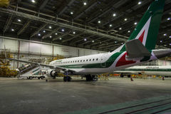 Alitalia Embraer in Hangar by night Stock Photography