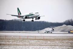 Alitalia Airbus A319-100 EI-IMO taking off in winter. Alitalia plane taking off from Munich Airport MUC, winter time with snow on runway Stock Images