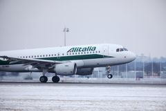 Alitalia Airbus A319-100 EI-IMO taking off in winter. Alitalia plane taking off from Munich Airport MUC, winter time with snow on runway Royalty Free Stock Images
