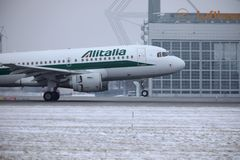 Alitalia Airbus A319-100 EI-IMO taking off in winter. Alitalia plane taking off from Munich Airport MUC, winter time with snow on runway Royalty Free Stock Image