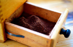 Alive ground coffee. Fresh milled coffee in an old fashioned coffee mill Stock Photo