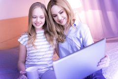 Alive mom and daughter hugging and looking at the laptop Royalty Free Stock Photos