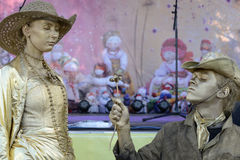 Alive sculpture western style romantic performance. A young man is giving a flower to his lover during their performance as alive sculptures Stock Photo