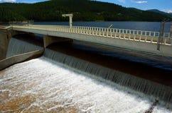 Aliviadero de la presa del depósito con agua que vierte sobre el top en el MES Imagen de archivo libre de regalías