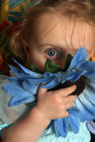 Alizia. Shy girl hiding behind a blue flower Stock Image