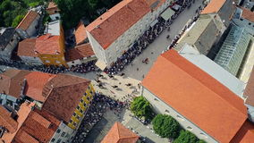 Alka procession in Sinj, aerial shot. SINJ, CROATIA - August 3, 2014: Copter aerial view of the Alka procession passes through the town. Part of memorial knight stock video footage