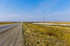 Alkali lake on the prairie in Saskatchewan. A white alkali lake on the prairie under a blue sky along side the highway near Swift Current, Saskatchewan, Canada Royalty Free Stock Images