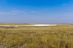 Alkali lake on the prairie in Saskatchewan. A white alkali lake on the prairie under a blue sky near Swift Current, Saskatchewan, Canada Royalty Free Stock Photos