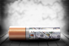 Alkaline battery with dollars on grunge background Stock Photo
